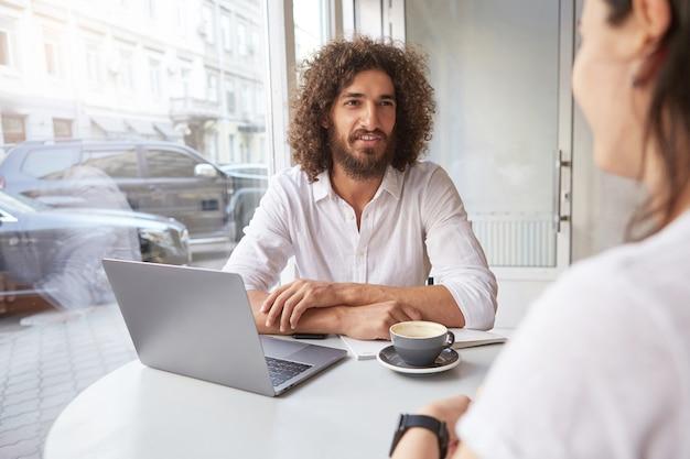 Joven apuesto hombre de negocios con barba que tiene cita fuera de la oficina, que tiene una conversación agradable en la cafetería mientras toma café, con camisa blanca