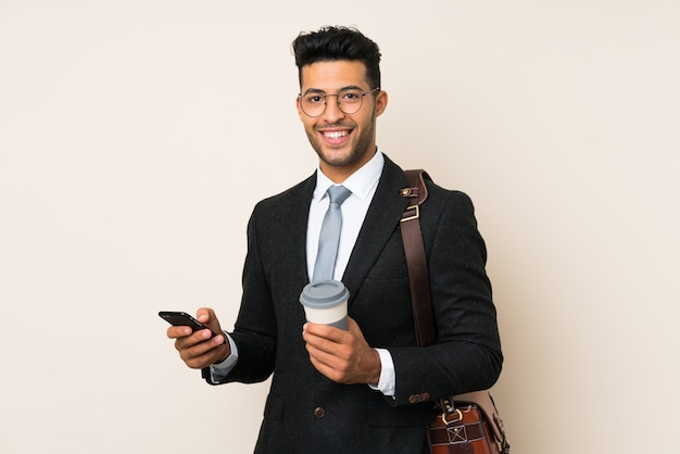 Joven apuesto hombre de negocios con café para llevar sobre fondo aislado