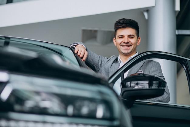 Joven apuesto hombre de negocios elegir un automóvil en una sala de exposición de automóviles