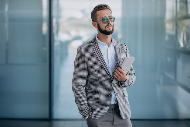 Joven apuesto hombre de negocios en la oficina con tableta