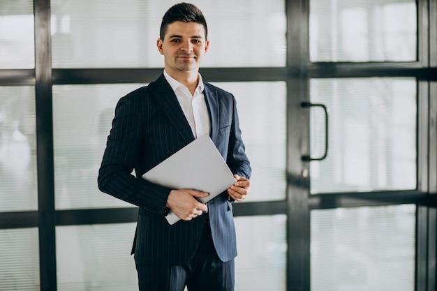 Joven apuesto hombre de negocios con ordenador portátil en la oficina