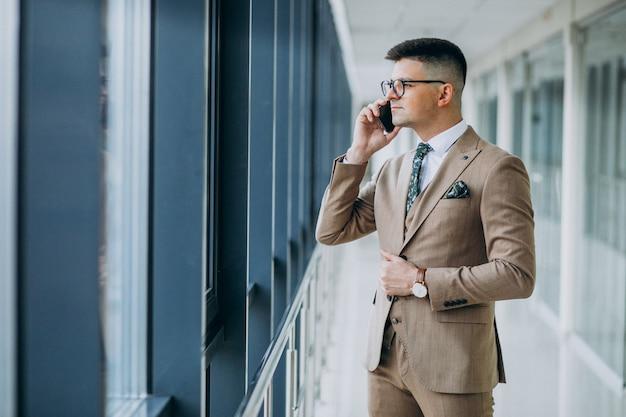 Joven apuesto hombre de negocios de pie con el teléfono en la oficina