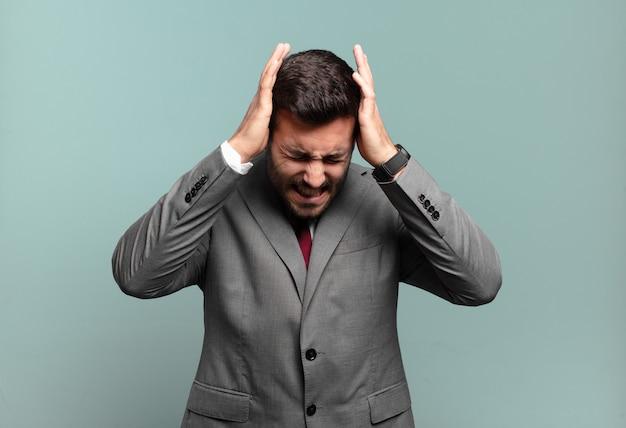 Joven apuesto hombre de negocios que se siente estresado y frustrado, levantando las manos a la cabeza, sintiéndose cansado, infeliz y con migraña