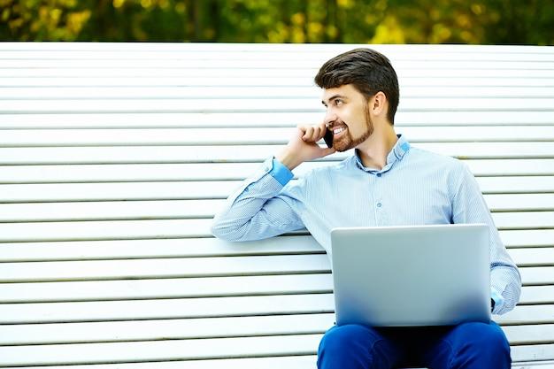 Joven apuesto hombre de negocios sonriente modelo sentado en el banco del parque usando la computadora portátil en tela casual hipster hablando por teléfono móvil