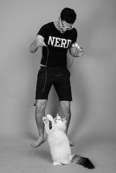 Joven apuesto hombre nerd persa con anteojos contra la pared gris en blanco y negro