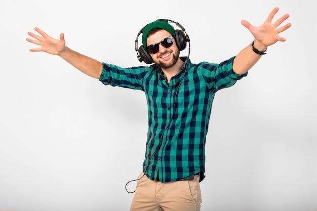 Joven apuesto hombre sonriente feliz escuchando música en auriculares aislado sobre fondo blanco de estudio, vistiendo camisa y gafas de sol