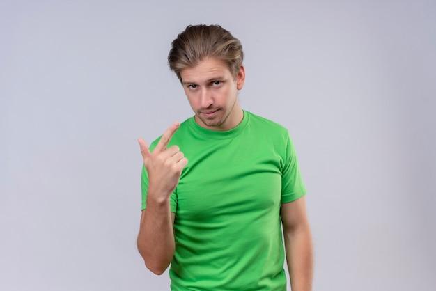 Joven apuesto hombre vestido con camiseta verde apuntando con el dedo a sí mismo con expresión de confianza de pie sobre la pared blanca