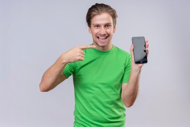 Joven apuesto hombre vestido con camiseta verde sosteniendo y mostrando el teléfono inteligente apuntando con el dedo sonriendo alegremente de pie sobre la pared blanca