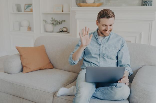 Joven apuesto hombre vestido casualmente agitando su mano mientras habla con su familia en línea usando un cuaderno, feliz de tener una conversación con familiares, sentado en el sofá con la pierna cruzada