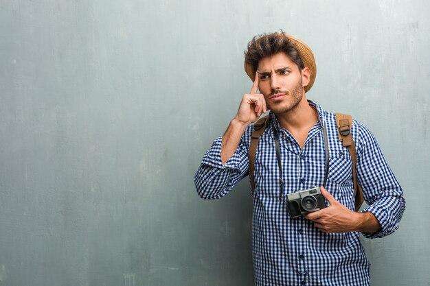 Un joven y apuesto hombre viajero que llevaba un sombrero de paja, una mochila y una cámara de fotos pensando y mirando hacia arriba, confundido por una idea, intentaría encontrar una solución.