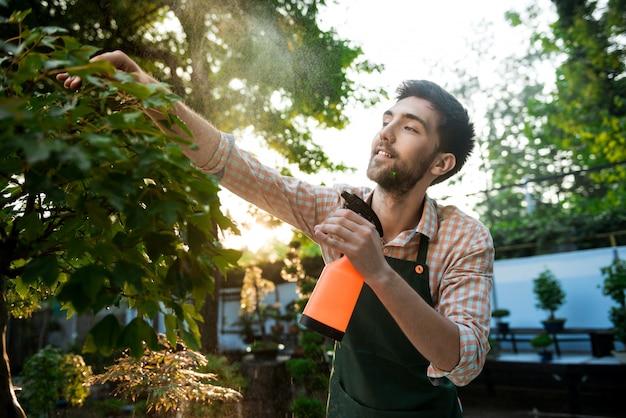 Joven apuesto jardinero alegre sonriendo, regando, cuidando las plantas