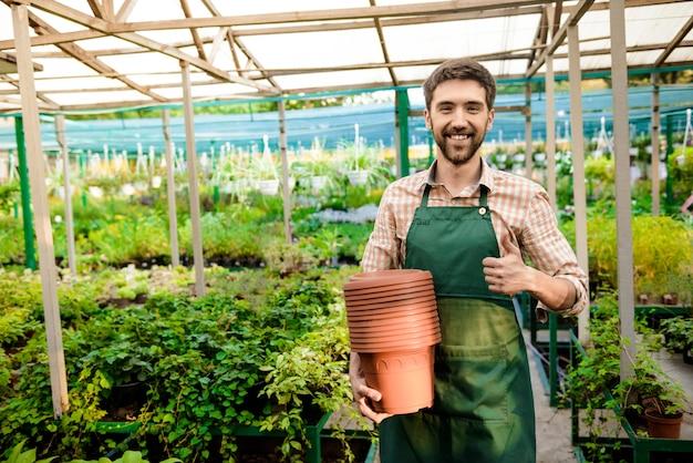 Joven apuesto jardinero alegre sonriendo, sosteniendo macetas, mostrando bien entre las plantas