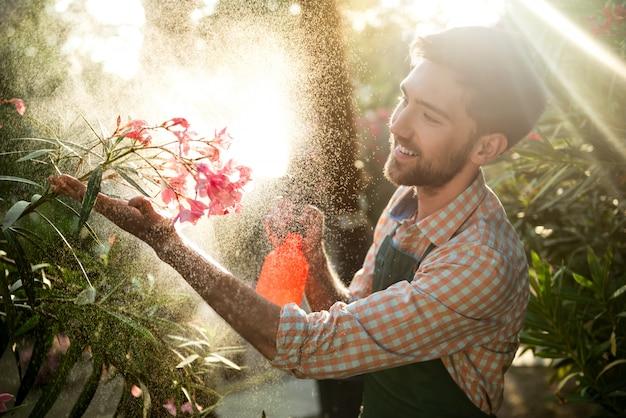 Joven apuesto jardinero sonriendo, regando, cuidando las flores