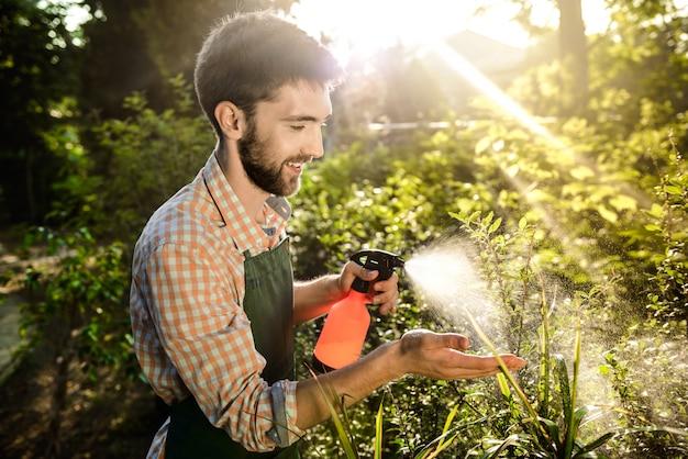 Joven apuesto jardinero sonriendo, regando, cuidando las plantas