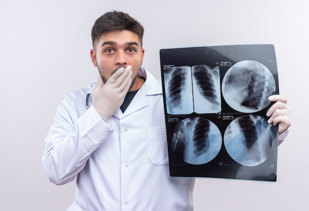 Joven apuesto médico con bata médica blanca, guantes médicos blancos y estetoscopio asustado sosteniendo tomografía de pie sobre una pared blanca