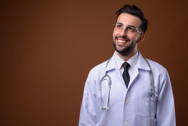 Joven apuesto médico iraní barbudo contra la pared marrón