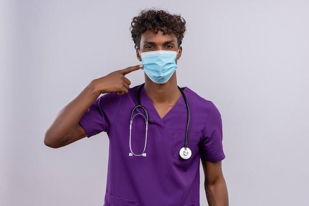 Un joven apuesto médico de piel oscura con cabello rizado vistiendo uniforme violeta con estetoscopio mostrando mascarilla