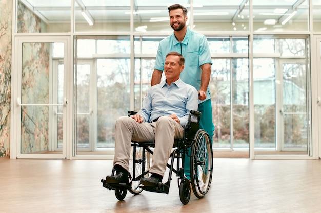 Un joven apuesto médico con su anciano discapacitado en silla de ruedas recorre los pasillos de una clínica moderna.