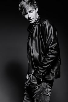 Joven apuesto musculoso hombre modelo masculino en chaqueta de cuero posando en el estudio mostrando sus músculos abdominales