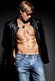 Joven apuesto musculoso hombre modelo masculino posando en el estudio mostrando sus músculos abdominales en la chaqueta de cuero