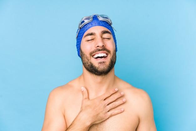 Joven apuesto nadador hombre aislado se ríe a carcajadas manteniendo la mano en el pecho