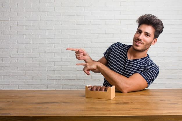 Joven apuesto y natural hombre sentado en una mesa que apunta a un lado, sonriendo sorprendido presentando algo, natural y casual. comiendo donuts de chocolate.