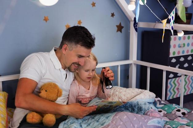 Joven apuesto padre y su hija leyendo un libro con una linterna mientras está sentado debajo de la cubierta en la cama