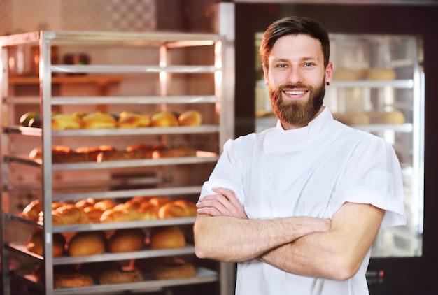 Joven apuesto panadero masculino en uniforme blanco