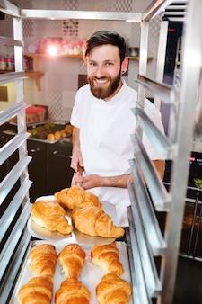 Un joven apuesto panadero tiene una bandeja con cruasanes franceses frente a una panadería y sonríe.