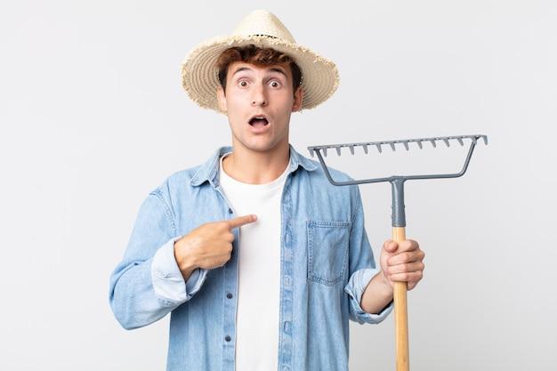 Joven apuesto que parece conmocionado y sorprendido con la boca abierta, apuntando a sí mismo. concepto de granjero