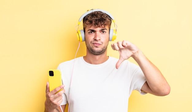 Joven apuesto sentimiento cruzado, mostrando los pulgares hacia abajo. concepto de auriculares y teléfono inteligente