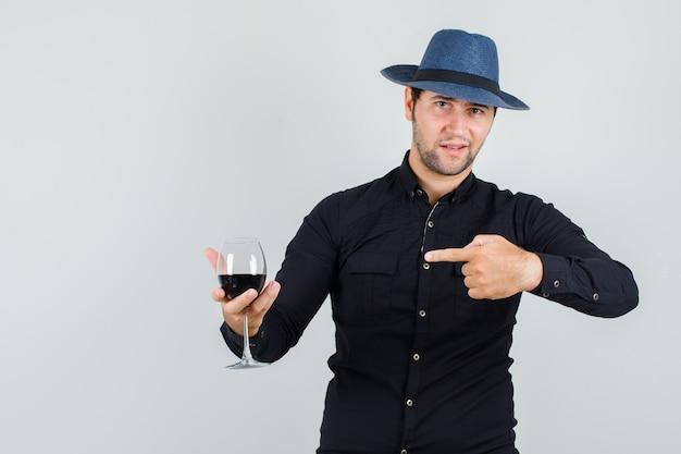 Joven apuntando al vaso de alcohol en camisa negra