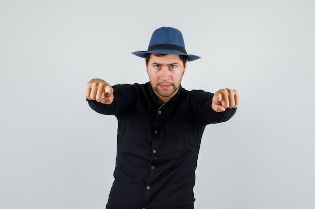 Joven apuntando a la cámara en camisa negra, sombrero y mirando estricto