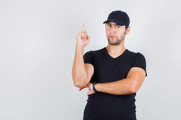 Joven apuntando con el dedo hacia arriba en camiseta negra, gorra y mirando curioso.