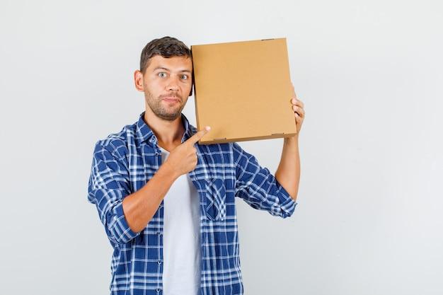 Joven apuntando con el dedo a la caja de cartón en camisa y mirando emocionado, vista frontal.
