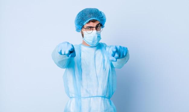 Joven apuntando hacia delante a la cámara con ambos dedos y expresión enojada, diciéndole que cumpla con su deber. concepto de coronavirus