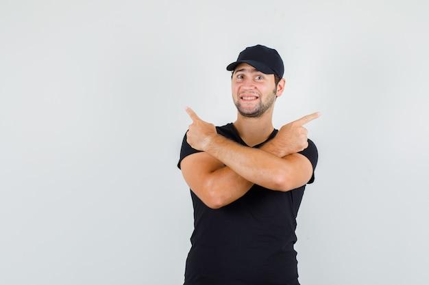 Joven apuntando a un lado en camiseta negra, gorra y mirando alegre.
