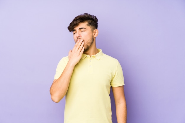 Joven árabe aislado en un espacio violeta bostezando mostrando un gesto cansado cubriendo la boca con la mano.
