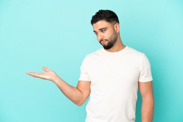 Joven árabe aislado sobre fondo azul sosteniendo copyspace con dudas