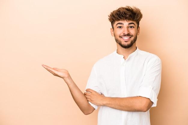 Joven árabe aislado sobre fondo beige mostrando un espacio de copia en una palma y sosteniendo otra mano en la cintura.