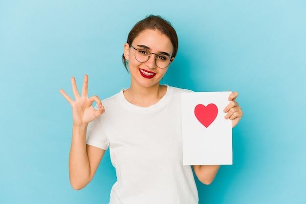Joven árabe flaca sosteniendo una tarjeta del día de san valentín alegre y confiada mostrando un gesto aceptable