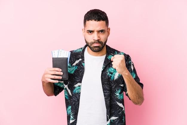Joven árabe fresco hombre sosteniendo una tarjeta de embarque aislado mostrando puño