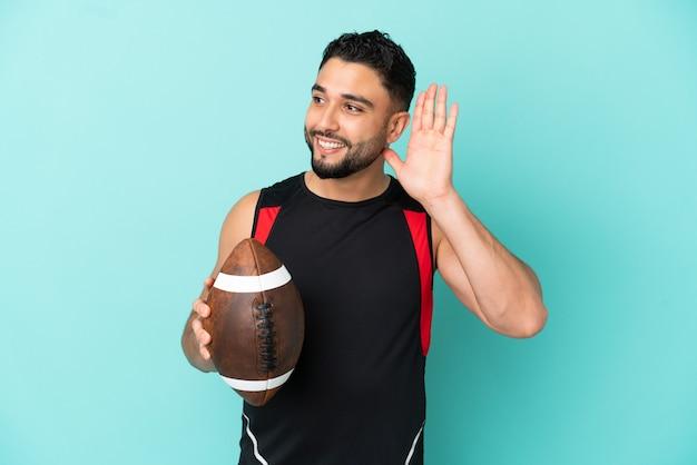 Joven árabe jugando rugby aislado sobre fondo azul escuchando algo poniendo la mano en la oreja