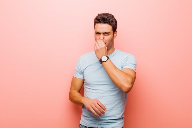 Joven árabe que se siente disgustado, tapando la nariz para evitar oler un hedor desagradable y desagradable contra la pared rosa