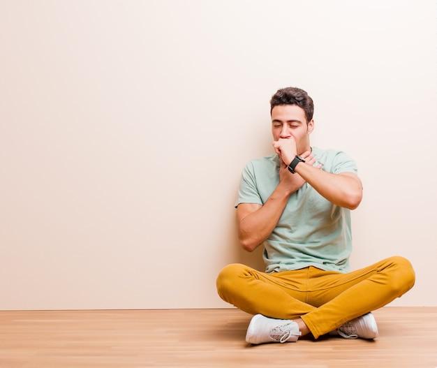 Joven árabe que se siente enfermo con dolor de garganta y síntomas de gripe, tos con la boca cubierta sentado en el suelo