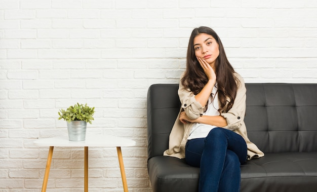 Joven árabe sentada en el sofá que está aburrida, fatigada y necesita un día de relax.