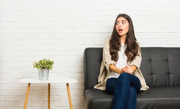Joven árabe sentada en el sofá sorprendida por algo que ha visto.