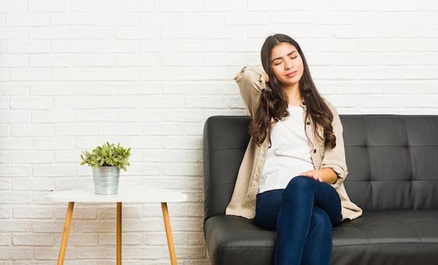 Joven árabe sentado en el sofá sufriendo dolor de cuello debido al estilo de vida sedentario.