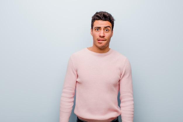 El joven árabe se siente desorientado, confundido e inseguro sobre qué opción elegir, tratando de resolver el problema contra la pared gris