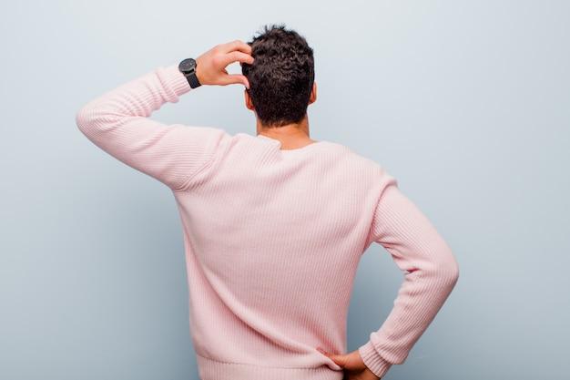 Joven árabe sintiéndose desorientado y confundido, pensando en una solución, con la mano en la cadera y otra en la cabeza, vista trasera contra la pared gris